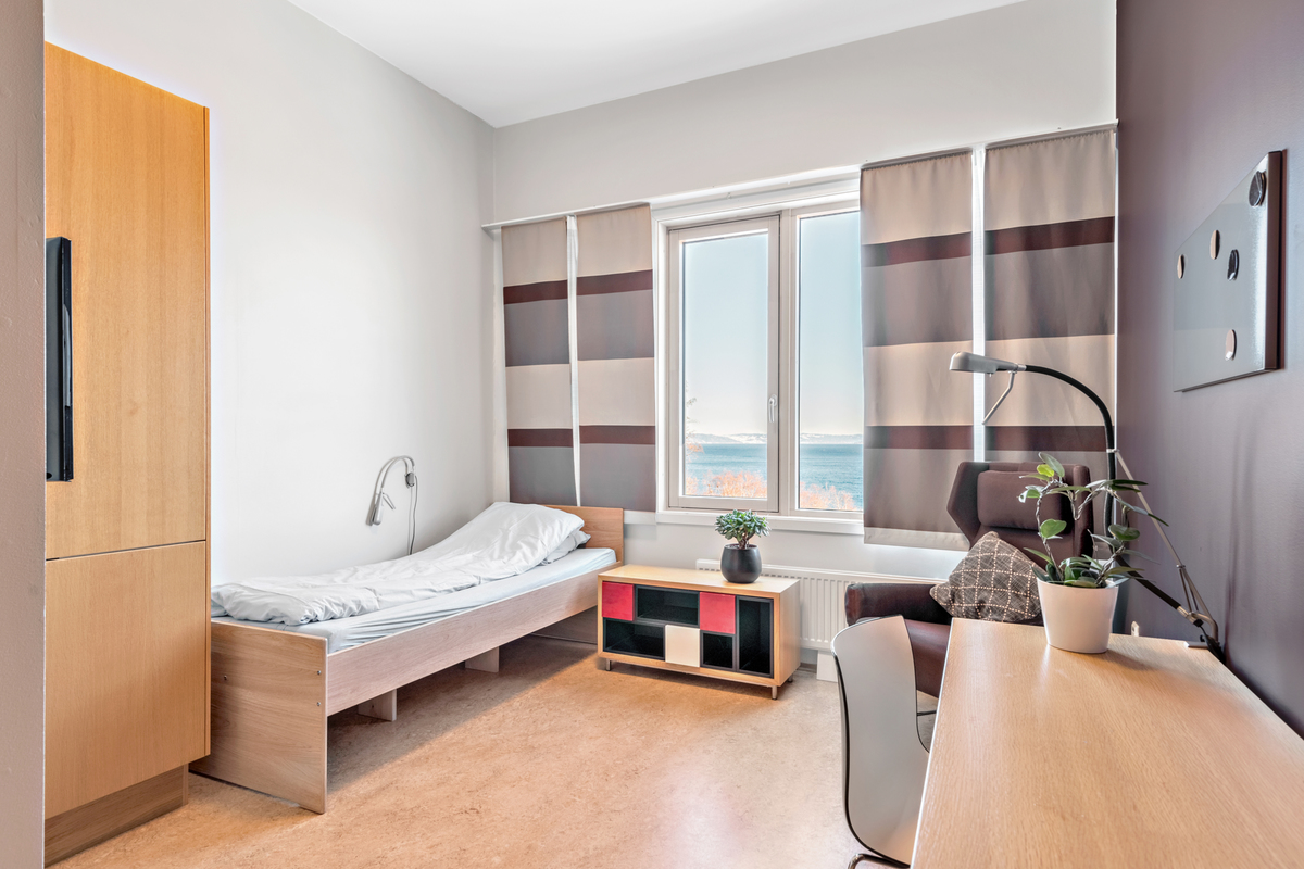 Foto av rom med en seng, et skrviebord, et klesskap og et nattbord. Rommet er stort og lyst.